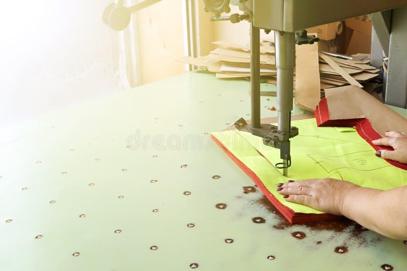 La lavoratrice su una fabbricazione di cucito usa il fabr elettrico di taglio fotografia stock libera da diritti