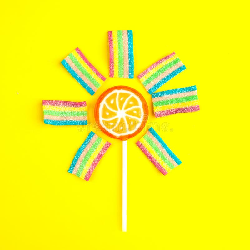 La lecca-lecca variopinta e la gelatina gradiscono un sole e un sole su fondo giallo luminoso Disposizione piana Concetto minimo  immagine stock