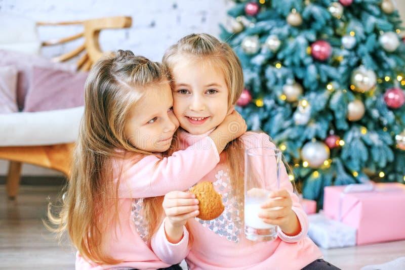 La leche de la bebida de los niños y come las galletas de harina de avena Abrazo de las muchachas Brea fotos de archivo libres de regalías