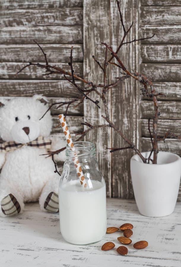 La leche de la almendra en una botella de cristal, las almendras y un juguete refieren una tabla de madera ligera fotografía de archivo