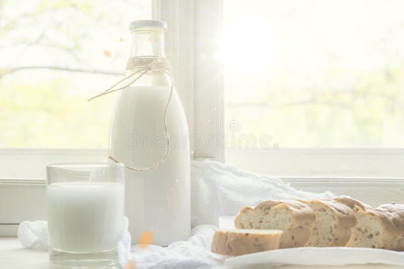 La leche de vaca cruda fresca en un travesa?o de la ventana, desayuno sano en el pueblo, vierte la leche en vidrio imagenes de archivo