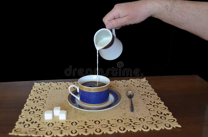 La leche se está vertiendo fuera de un jarro de leche derecho en una taza de café fotos de archivo libres de regalías