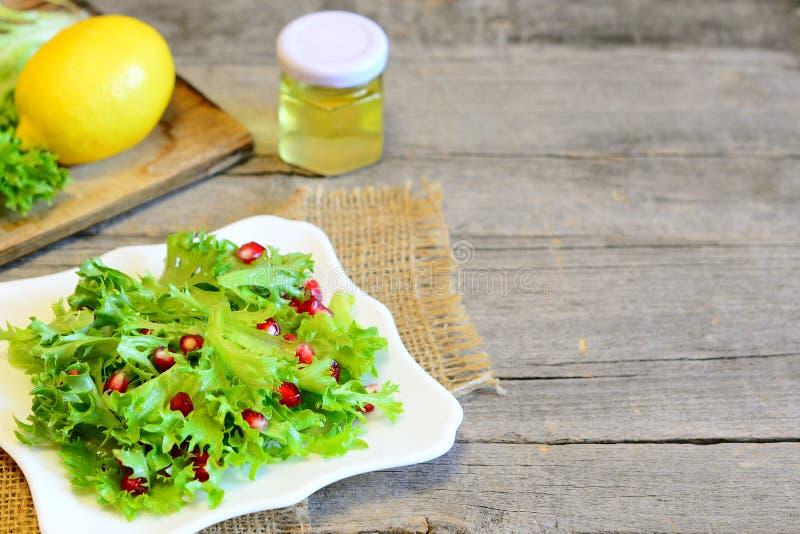 La lechuga de Frisee se va con las semillas de la granada vestidas con el jugo de limón y el aceite de oliva Receta fácil de la e imágenes de archivo libres de regalías
