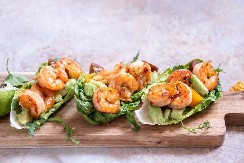 La lechuga envolvió los tacos del camarón con el tomate y el aguacate frescos fotos de archivo libres de regalías