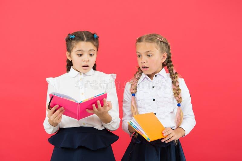 La lectura abre puertas Pequeños libros de lectura de los niños en fondo rojo Las niñas adorables aprenden la lectura en la escue imagenes de archivo