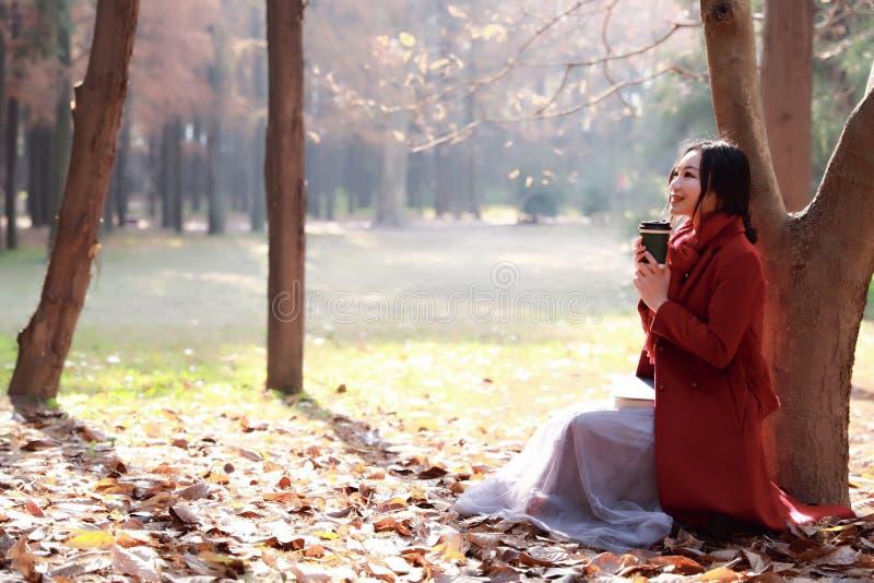 La lectura en naturaleza es mi afición, muchacha con el libro y té en el parque del otoño fotos de archivo libres de regalías
