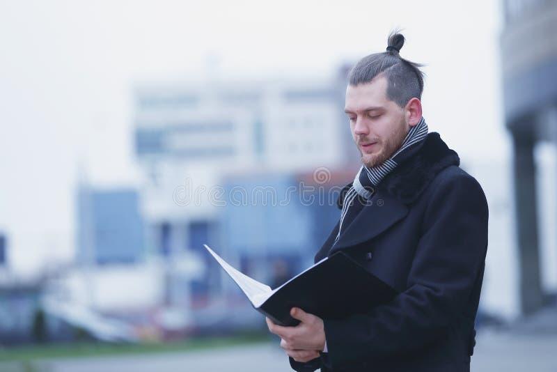 La lecture d'homme d'affaires documente la position sur une rue de ville photographie stock
