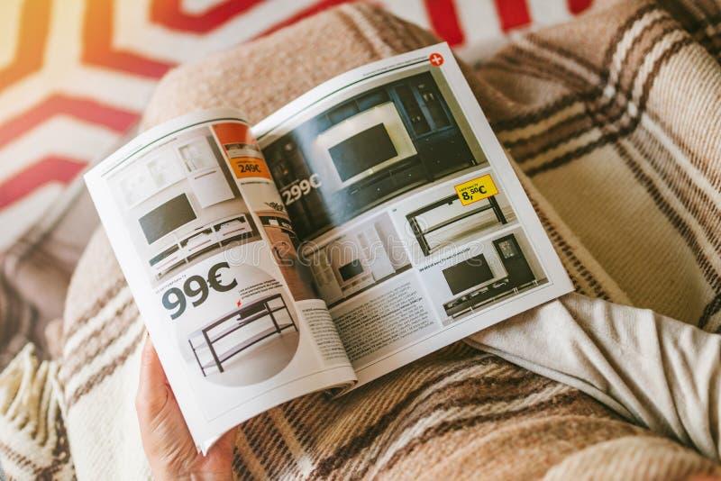 La lecture IKEA cataloguent la femme lue de la maison ci-dessus lue images stock