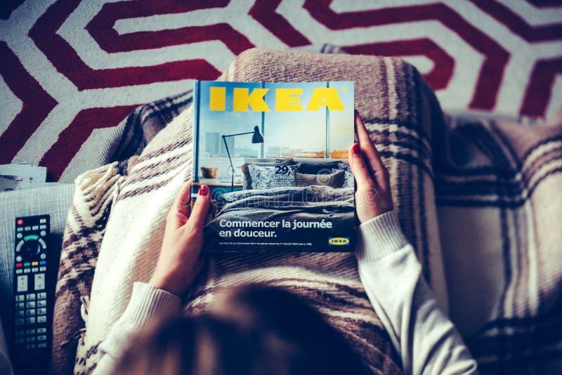 La lecture IKEA cataloguent la femme lue du catalogue ci-dessus photographie stock libre de droits