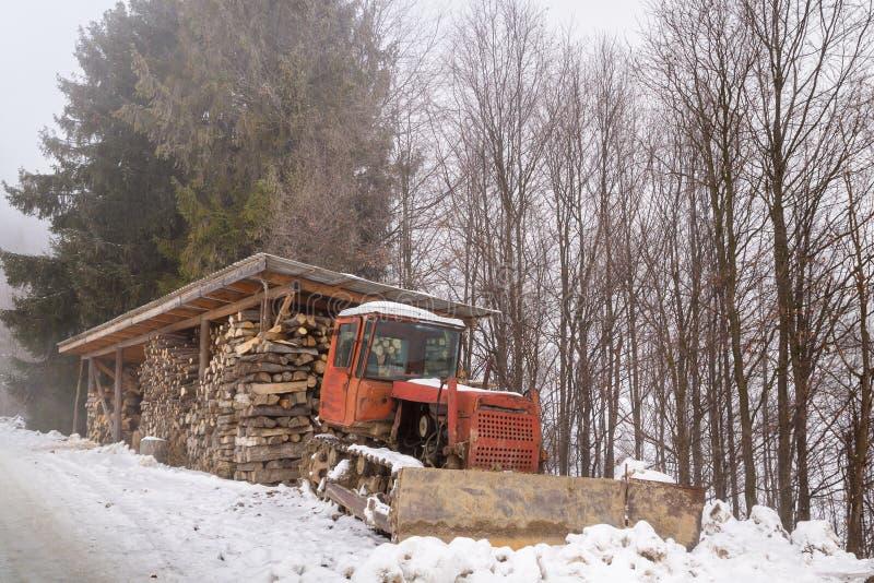 La legna da ardere ha raccolto per l'inverno e un bulldozer immagine stock