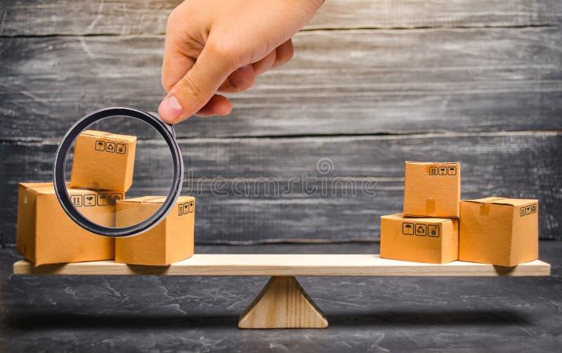 La lente d'ingrandimento sta esaminando i mucchi delle scatole sulle scale Bilancia commerciale e calcolo dal baratto importazion immagini stock