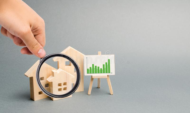 La lente d'ingrandimento sta esaminando le case di legno con un supporto dei grafici e delle informazioni Domanda crescente dell' fotografie stock