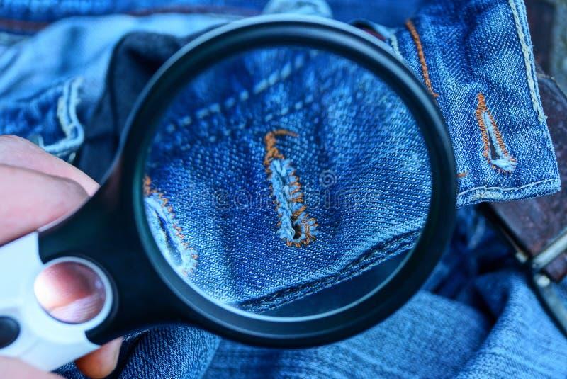 La lente nera aumenta il tessuto di cotone blu con un occhiello immagine stock libera da diritti