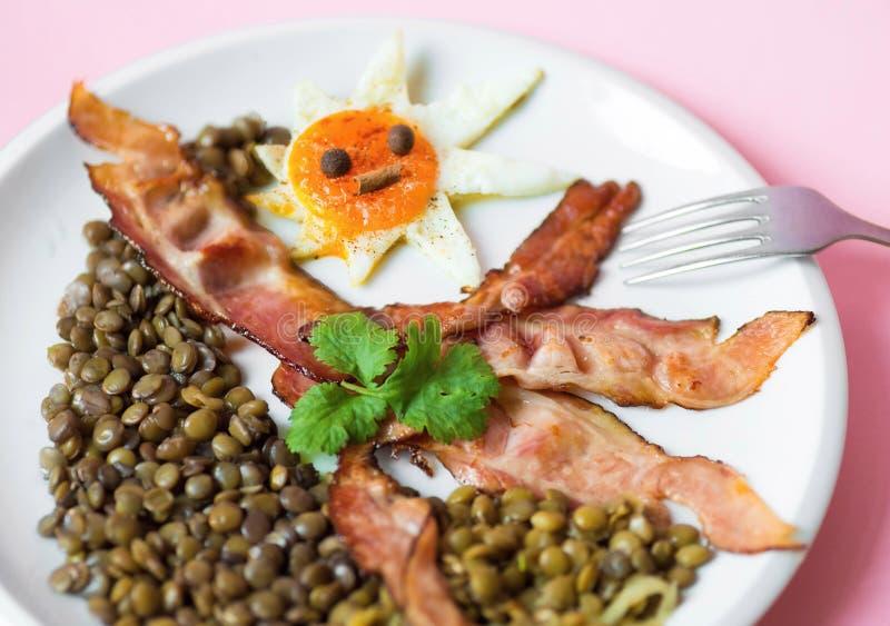 La lenticchia ed il bacon e l'uovo fritti hanno modellato il sole fotografia stock libera da diritti