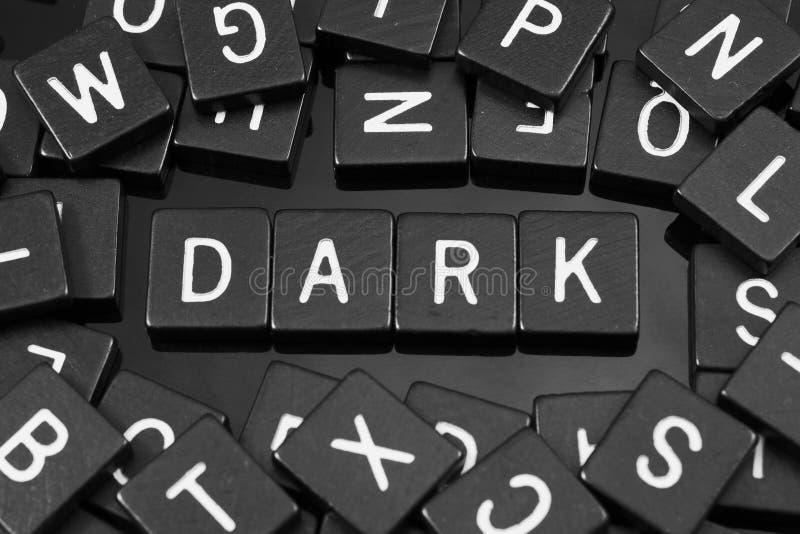 La letra negra teja el deletreo de la palabra y del x22; dark& x22; foto de archivo