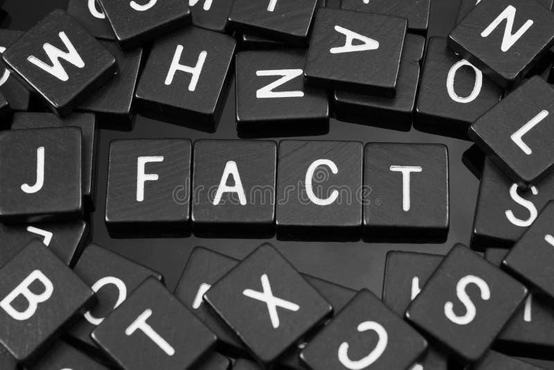 La letra negra teja el deletreo de la palabra y del x22; fact& x22; fotos de archivo