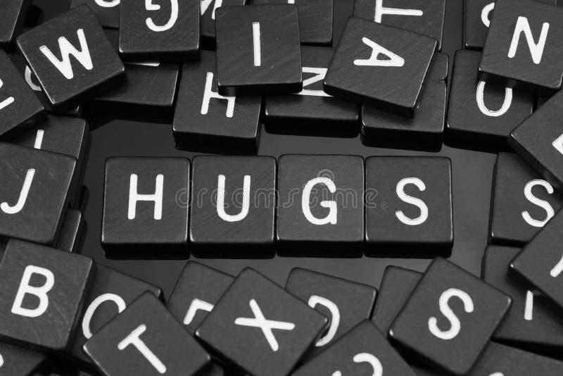 La lettera nera piastrella l'ortografia la parola & del x22; hugs& x22; fotografia stock