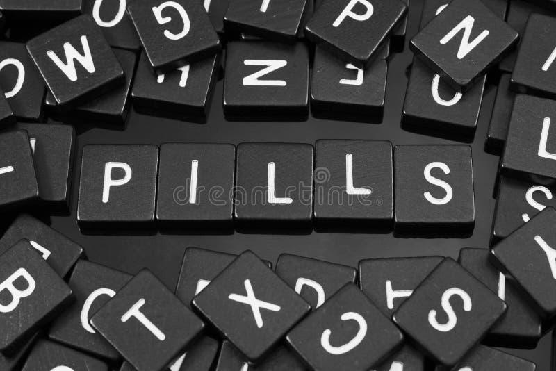 La lettera nera piastrella l'ortografia la parola & del x22; pills& x22; immagine stock