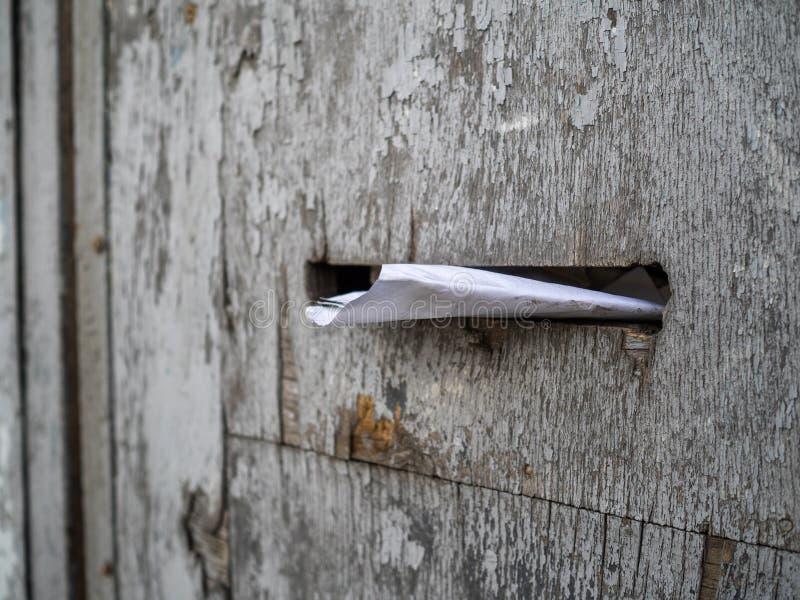 La lettera sgualcita si trova in una cassetta delle lettere Un vecchio recinto di legno con una cassetta delle lettere fotografia stock