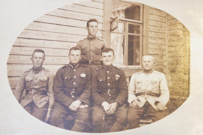 La Lettonie - les années 1930 : Une photo antique montre cinq soldats posant devant la maison en bois images libres de droits