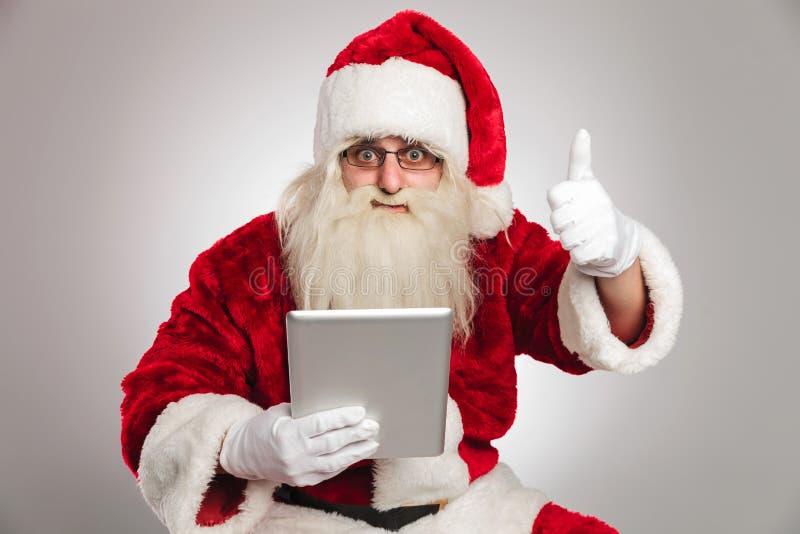 La lettura del Babbo Natale sulla compressa e fa il segno giusto immagini stock