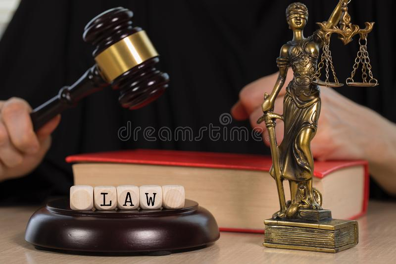 La LEY de la palabra integrada por de madera corta en cuadritos Mazo y estatua de madera de Themis en el fondo imágenes de archivo libres de regalías