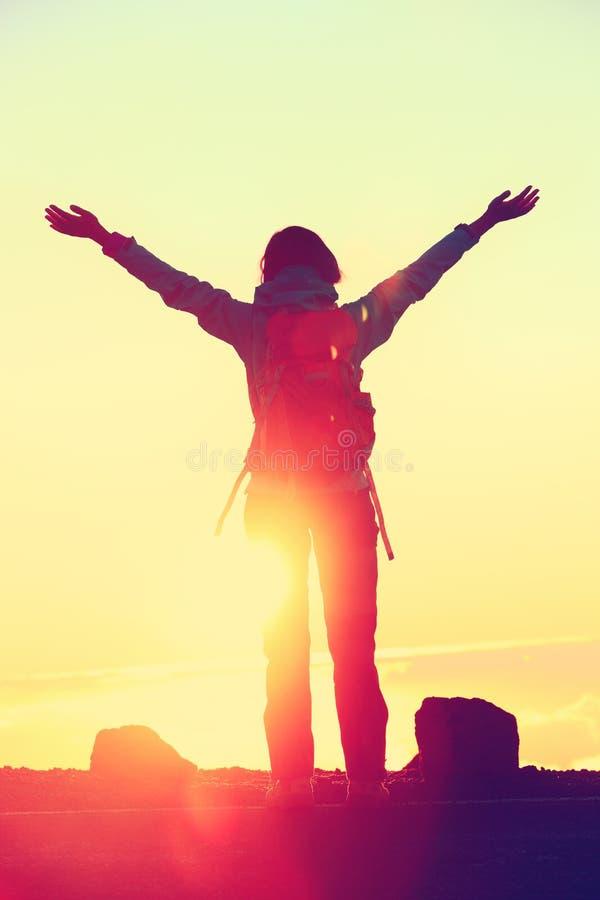 La libertà felice della siluetta della viandante arma su al tramonto fotografie stock libere da diritti
