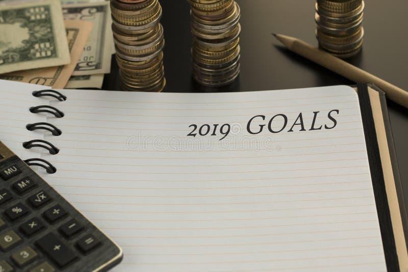 La libreta con 2019 metas manda un SMS, calculadora, lápiz, fondo del dinero foto de archivo libre de regalías