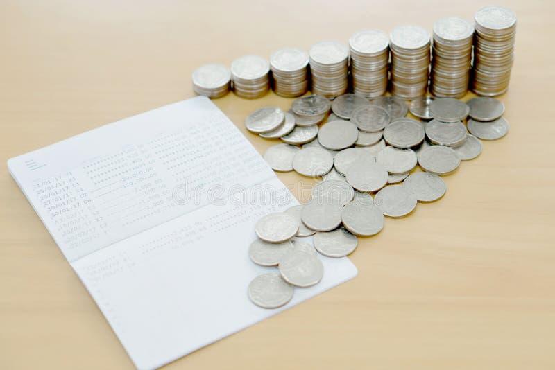 La libreta de banco y las monedas fotos de archivo