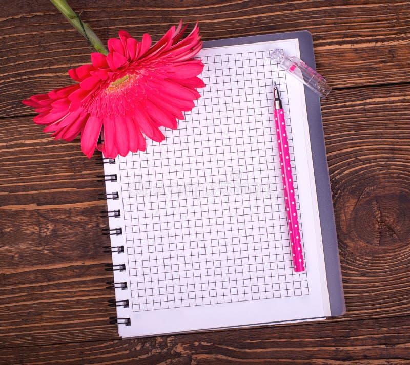 La libreta vacía, la pluma y el gerbera rosado florecen en un CCB de madera retro foto de archivo