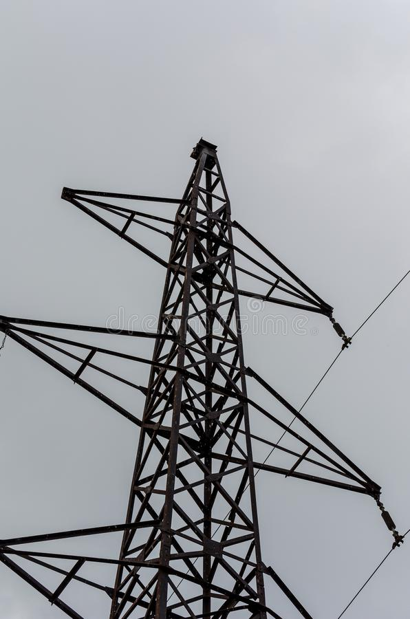 La ligne électrique fonctionne dans le ciel énorme, qui l'enveloppe doucement avec bruiner, pluie d'été images stock
