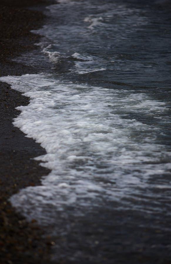 La ligne de vague de ressac sur un Pebble Beach foncé le soir photos libres de droits