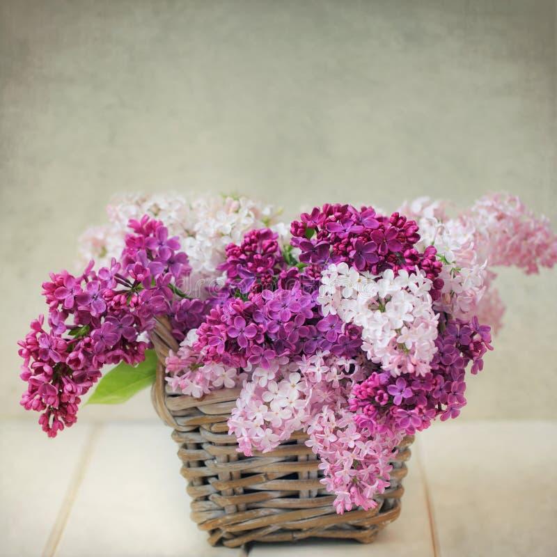 La lila del vintage florece el ramo en la cesta de Wisker imagen de archivo libre de regalías