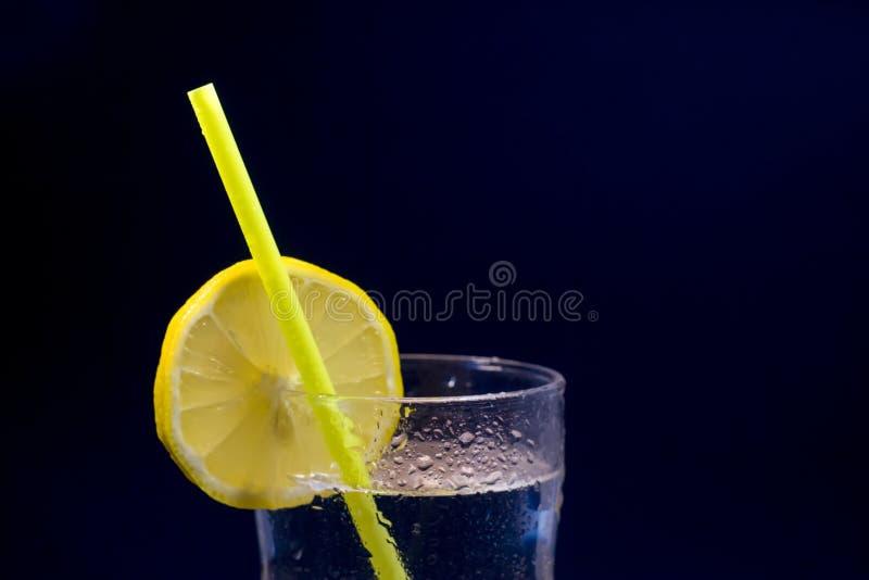 La limonada con la rebanada del limón y la paja de beber amarilla aisló el ove foto de archivo libre de regalías