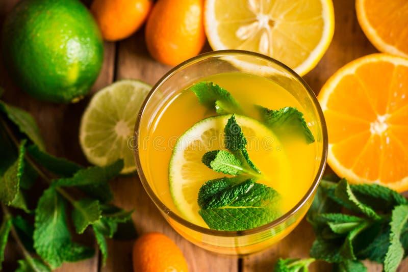 La limonada fresca de la fruta cítrica de naranjas abona la menta con cal fresca en el vidrio, visión superior, colores vibrantes fotos de archivo