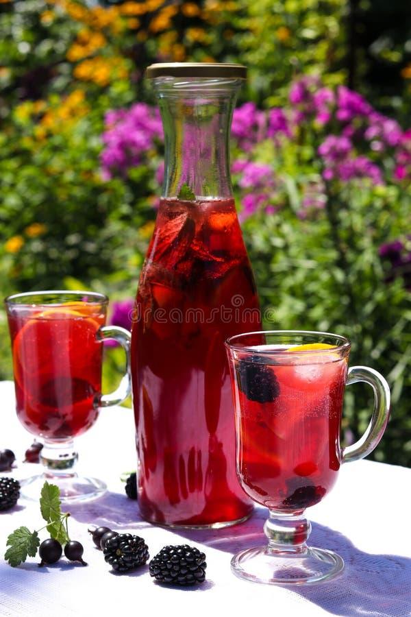 La limonada hecha en casa de la fruta está en una botella y vidrios en la tabla en el aire abierto imagen de archivo