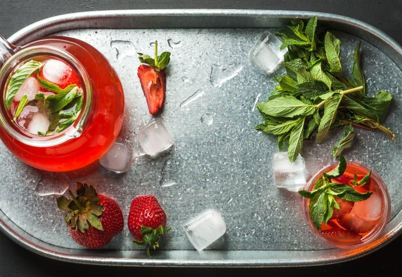 La limonata casalinga della fragola, menta e ghiaccio, è servito con le bacche fresche in vassoio del metallo, vista superiore fotografie stock
