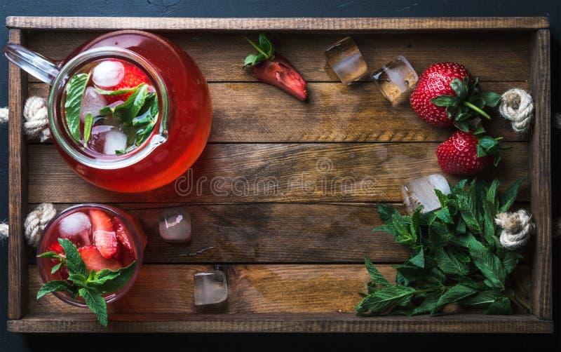 La limonata casalinga della menta della fragola servita con le bacche fresche e ghiaccia il fondo di legno, la vista superiore, s immagine stock