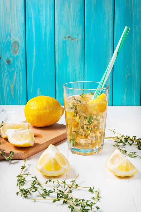 La limonata con timo è servito in vetro con una paglia su una tavola di legno bianca fotografia stock libera da diritti