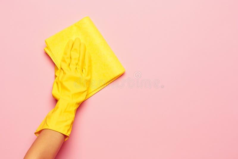 La limpieza de la mano del ` s de la mujer en un fondo rosado Concepto de la limpieza o de la economía doméstica foto de archivo libre de regalías