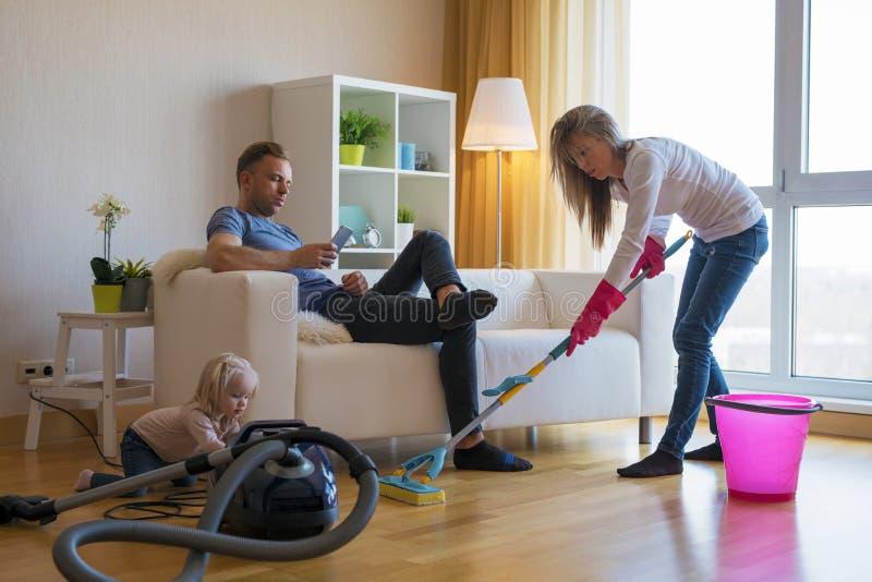 La limpieza de la mujer suela en casa mientras que su hombre perezoso que se sienta en sofá imagen de archivo libre de regalías