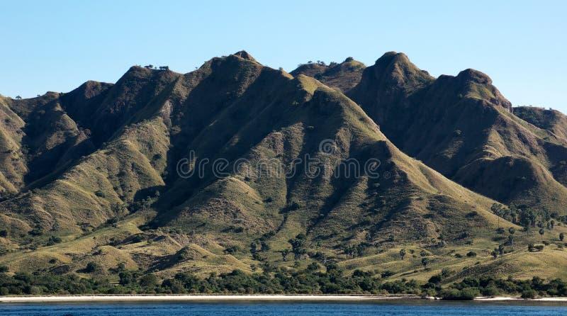 La linea costiera delle montagne con vegetazione verde e l'oceano blu innaffiano a Labuan Bajo in Flores immagini stock