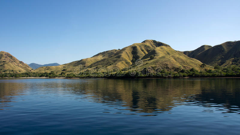 La linea costiera delle montagne con vegetazione verde ha riflesso in acqua blu dell'oceano a Labuan Bajo in Flores fotografie stock libere da diritti