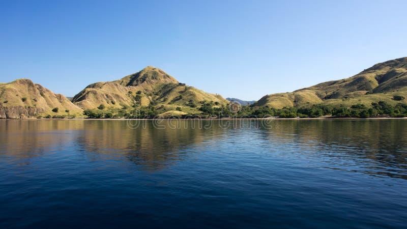 La linea costiera delle montagne con vegetazione verde ha riflesso in acqua blu dell'oceano a Labuan Bajo in Flores fotografia stock