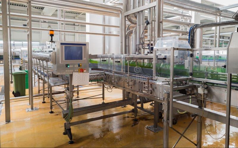 La linea di nastro trasportatore ha caricato con le bottiglie di birra in una fabbrica di birra fotografia stock
