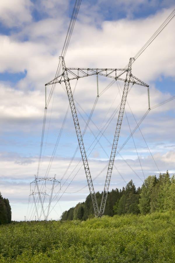 La linea elettrica ad alta tensione nei campi fotografia stock libera da diritti