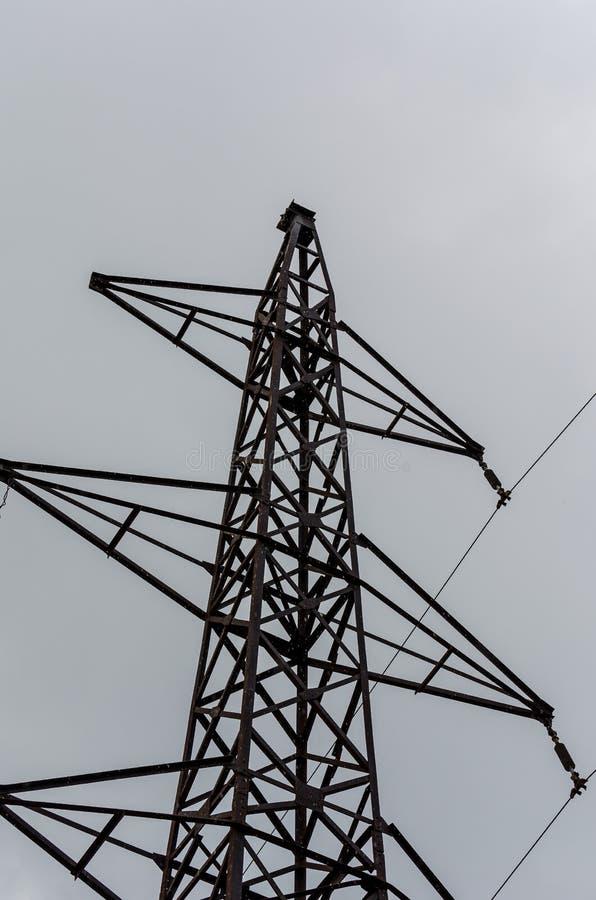 La linea elettrica si imbatte nel cielo enorme, che la avvolge delicatamente con una pioviggine, pioggia dell'estate immagini stock