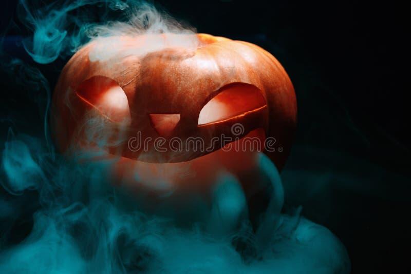 La linterna de la calabaza de Halloween con las hojas secas con la quema observa fotografía de archivo libre de regalías