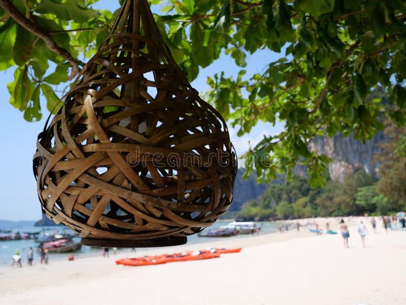 La linterna en el árbol sobre siluetas borrosas de la gente en la playa fotografía de archivo