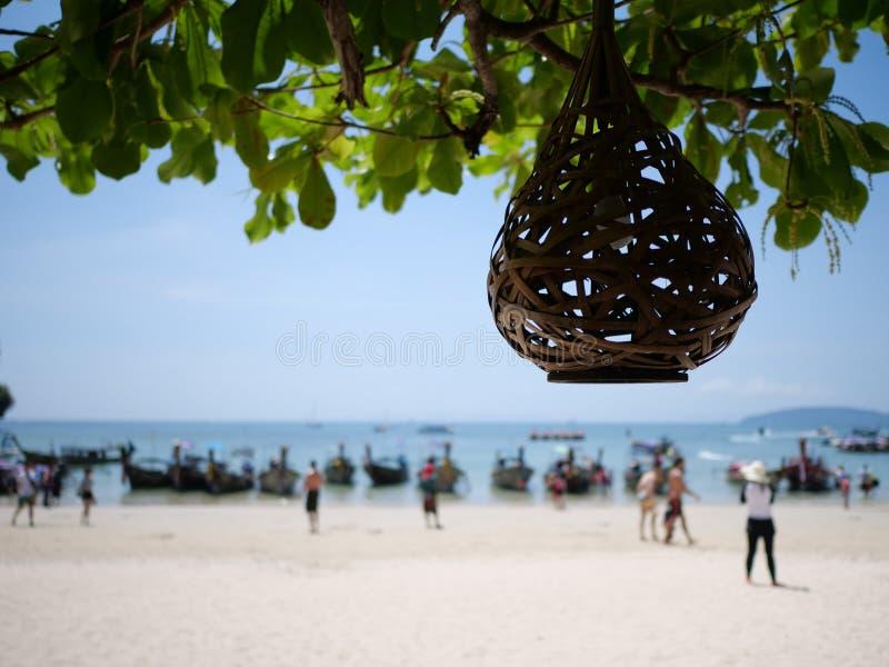 La linterna en el árbol sobre siluetas borrosas de la gente en la playa imágenes de archivo libres de regalías